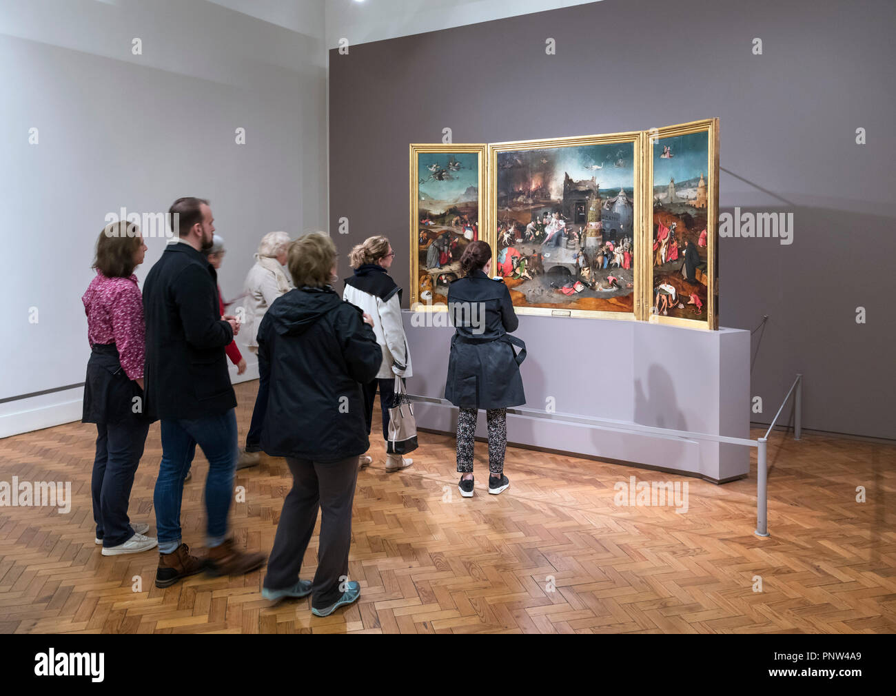 Visitors looking at the painting 'The Temptation of St Anthony' by Hieronymus Bosch, Museu Nacional de Arte Antiga (National Museum of Ancient Art) Li - Stock Image
