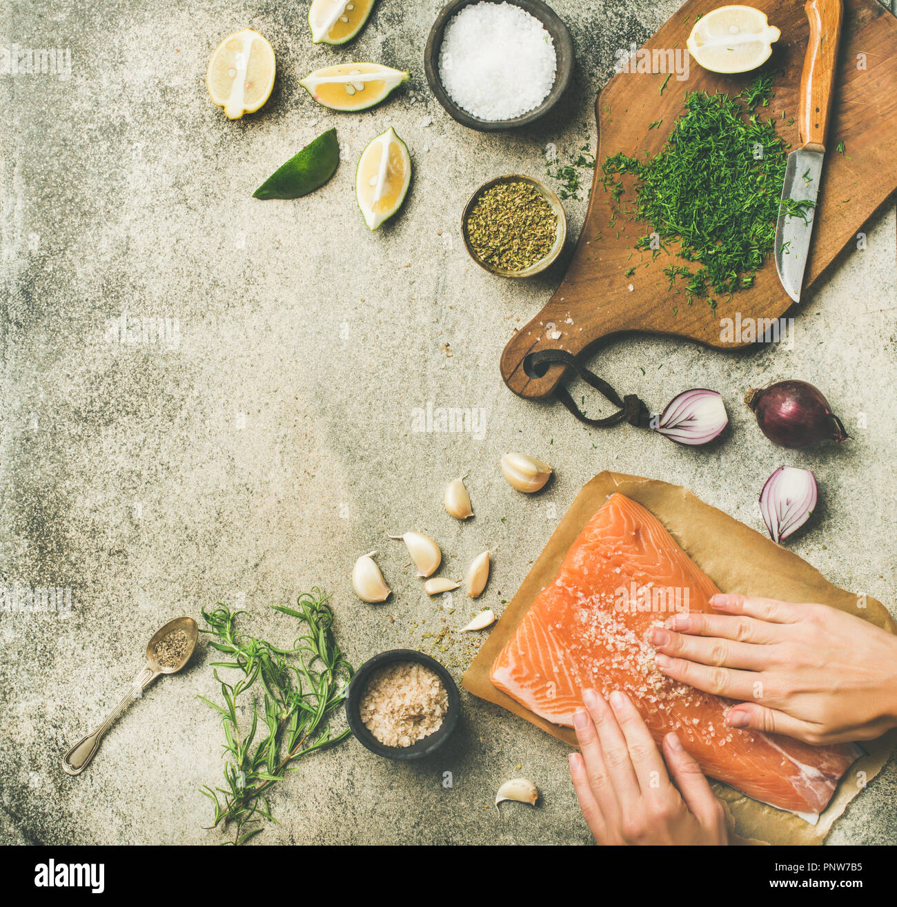 Female hands cooking salted salmon fish fillet on grey table - Stock Image