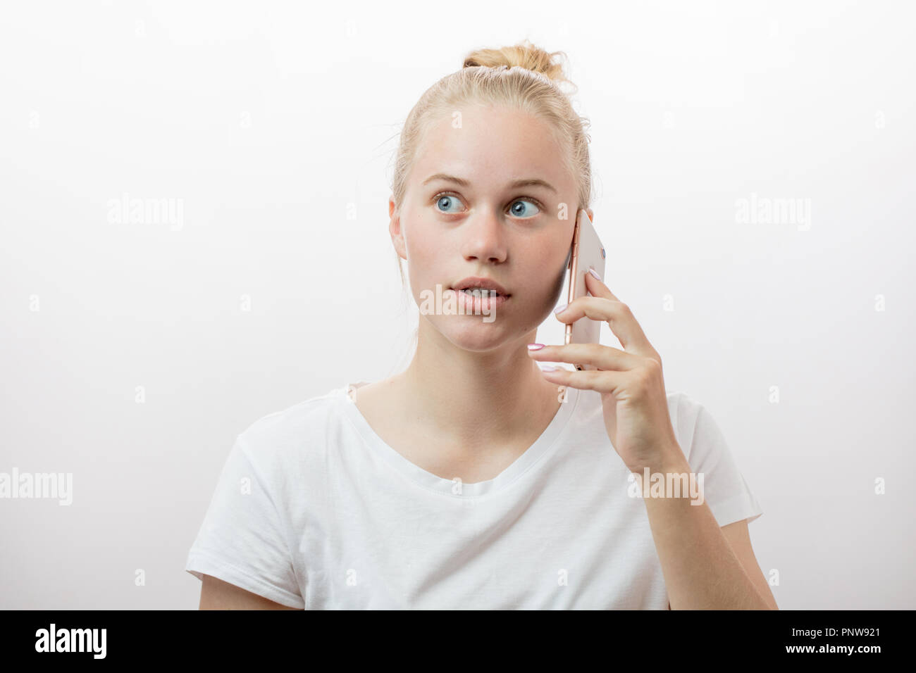 Surprised upset young blonde woman with her smart phone - Stock Image