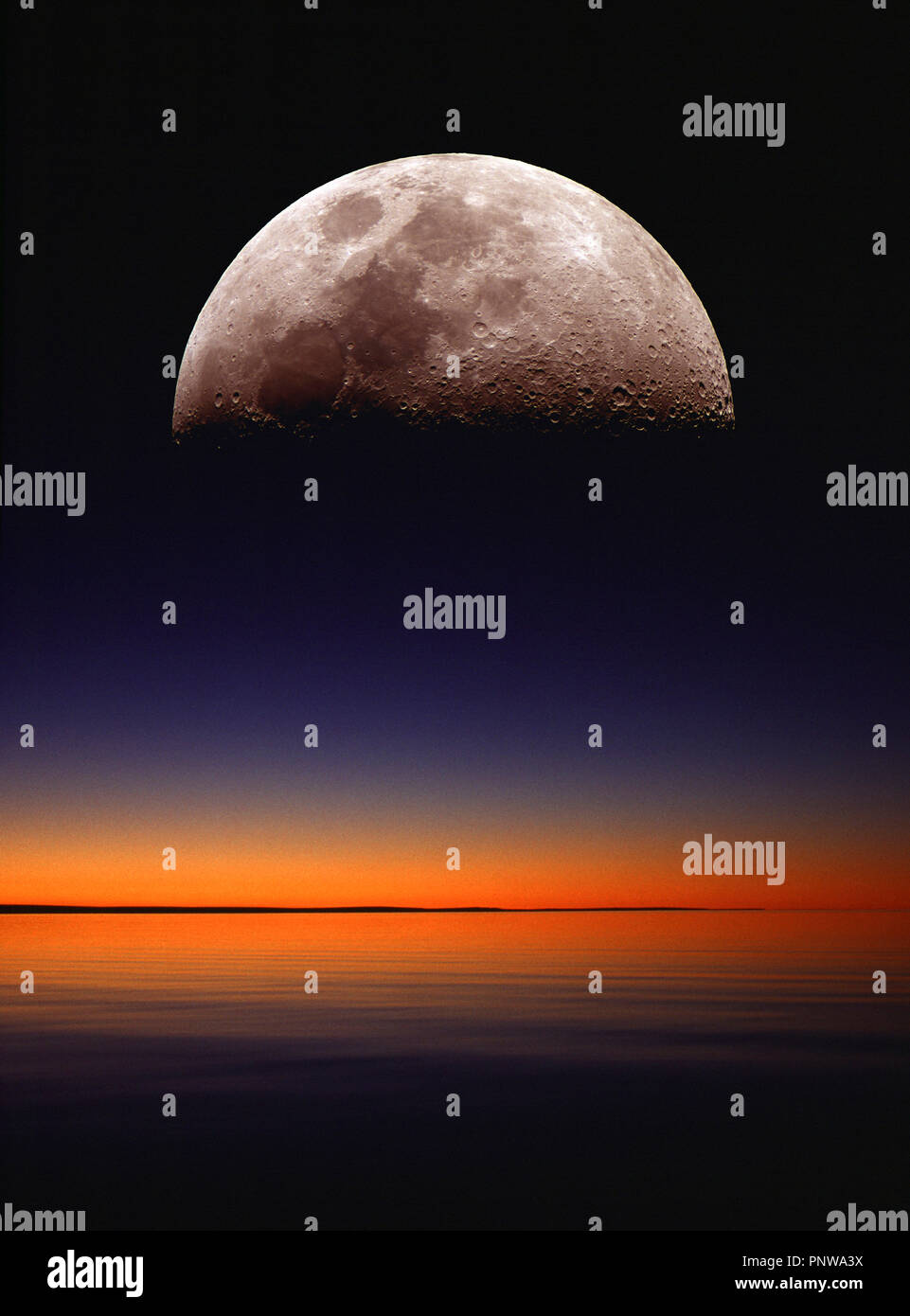 Concept art photograph of the moon rising above a seascape horizon at dawn. Stock Photo
