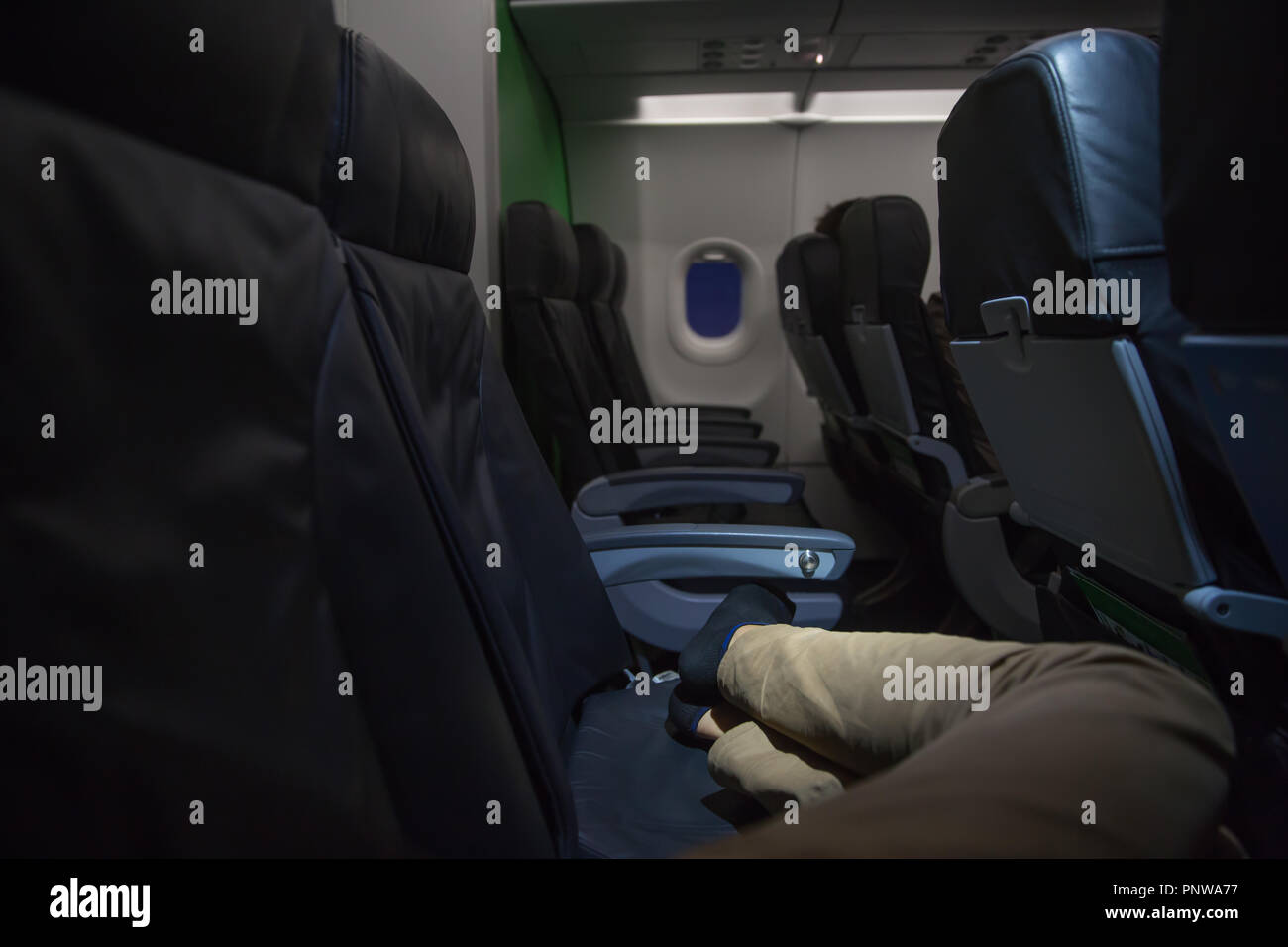 Unrecognizable man sleeps on economy seats in a plane. Close up of legs in aircraft. Travel concept Stock Photo