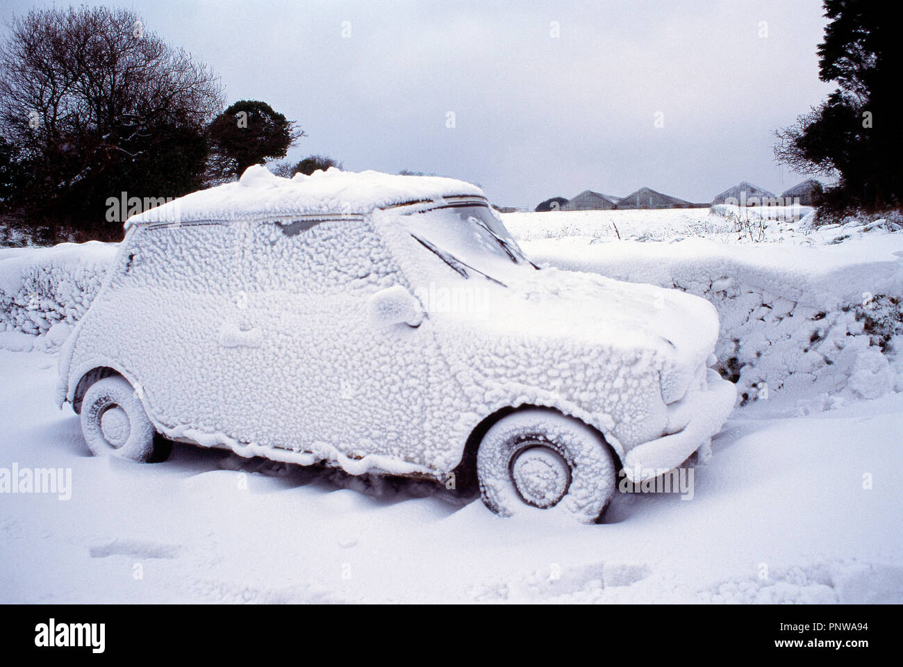 Winter scene with mini car covered in snow. Channel Islands. Guernsey. - Stock Image