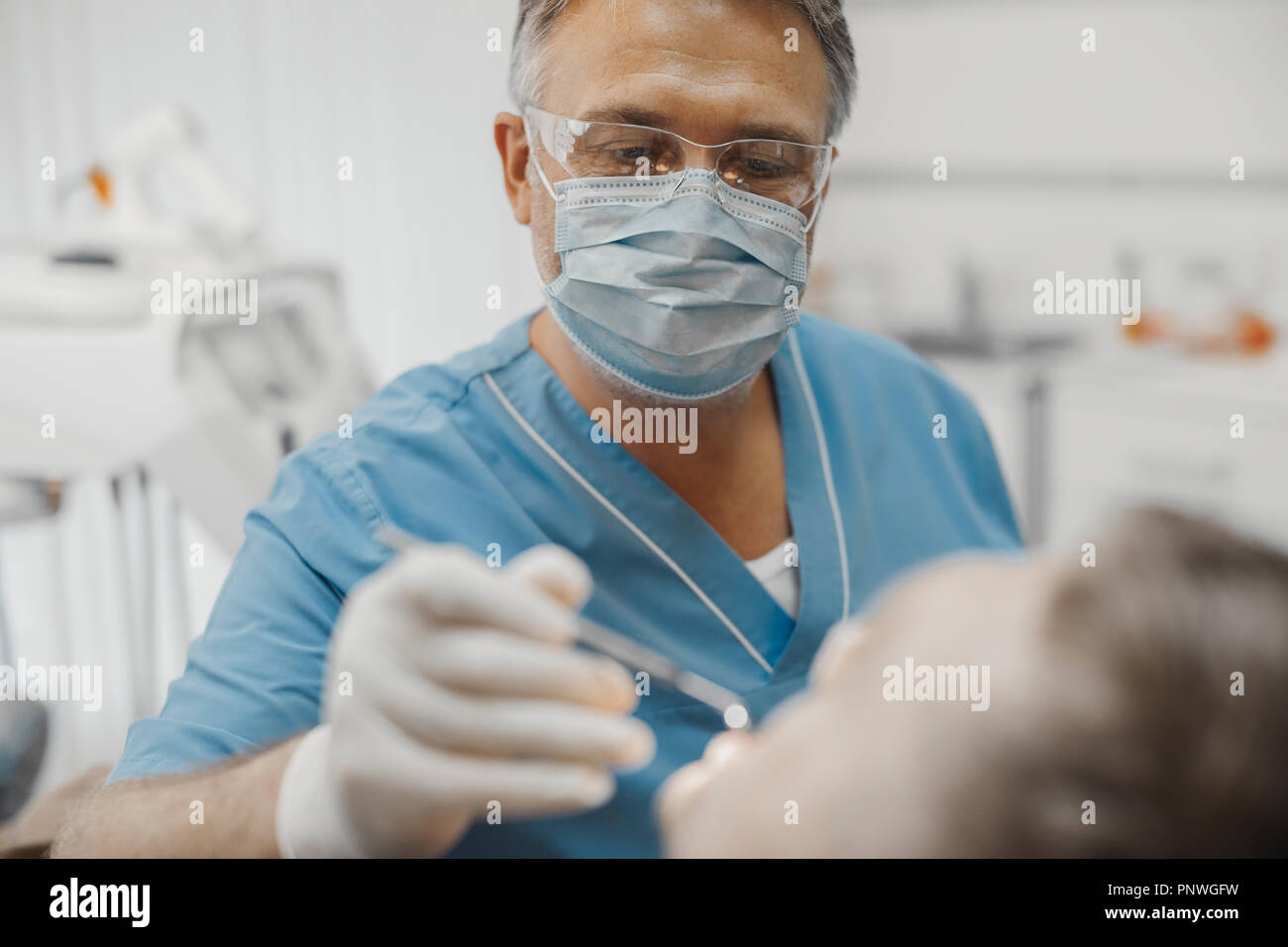 Close up of dentist in blue uniform checking up client teeth health condition. - Stock Image