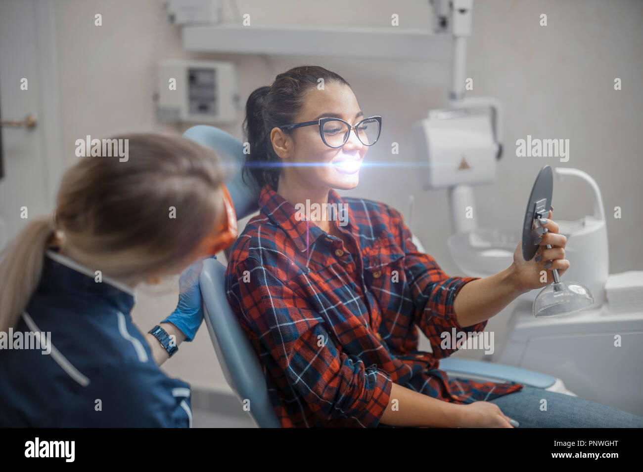 Close up of woman dentist and young woman client holding mirror and smiling. - Stock Image