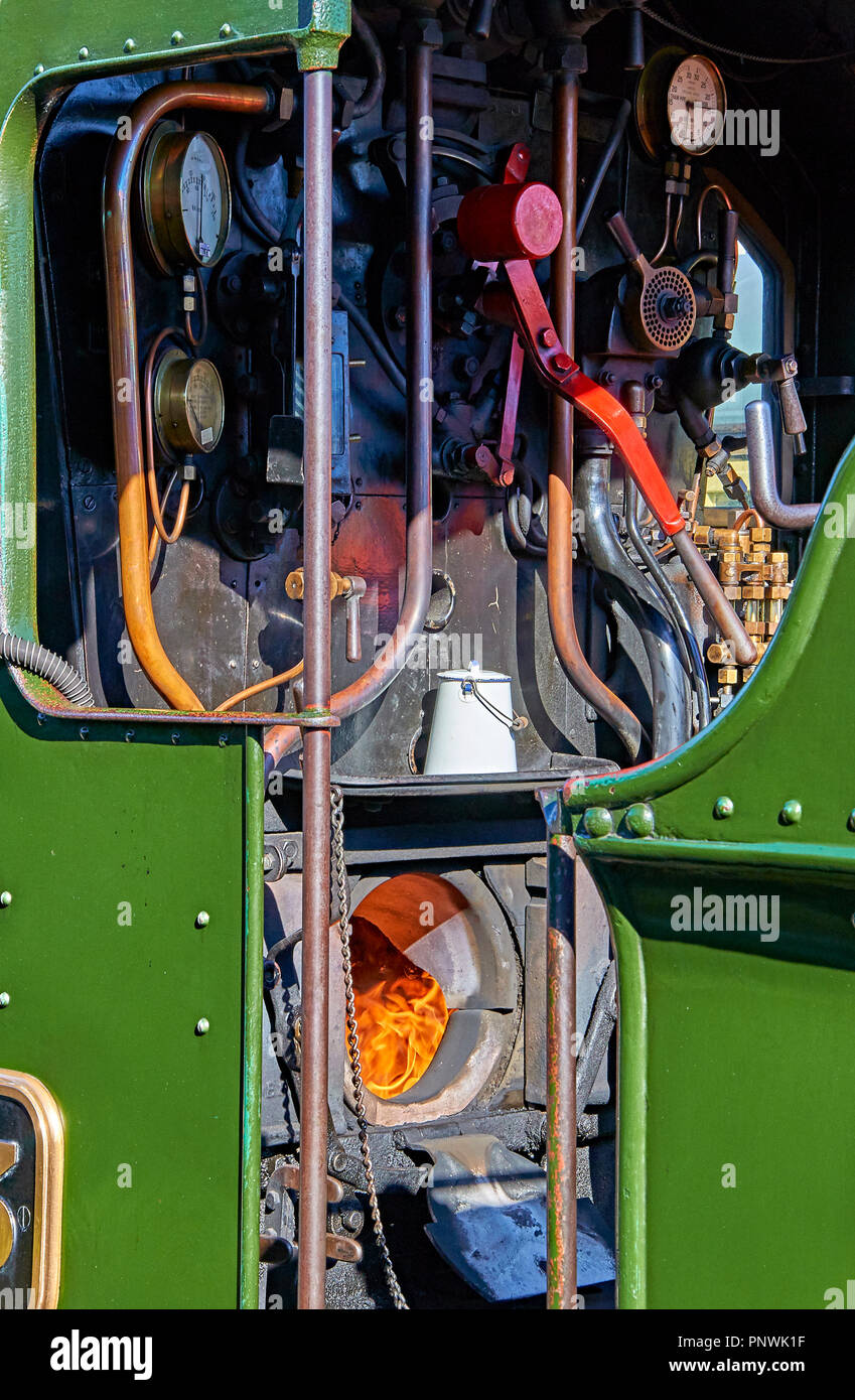 View into the driver's compartment of a fully restored working steam locomotive, showing flames burning in the firebox Stock Photo