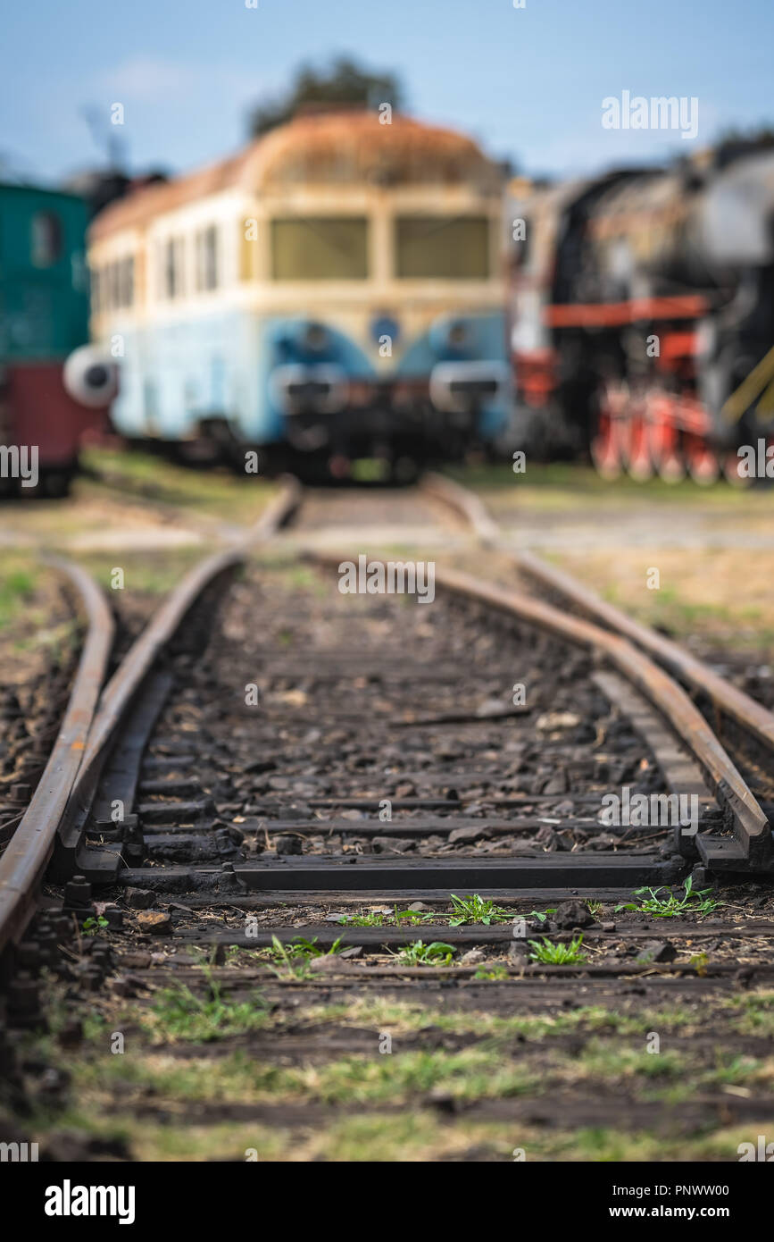 Shallow depth of field closeup of the rail tracks with old disused locomotives and carriages in the background Stock Photo