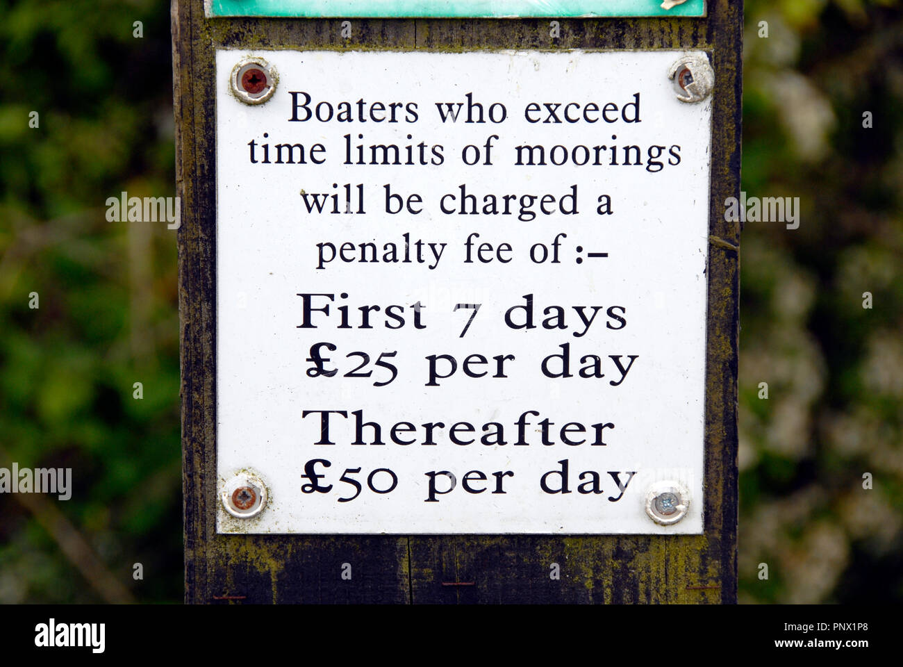 Close up of sign showing penalties for overstaying time limits for mooring on Kennet & Avon canal, Wiltshire, England - Stock Image