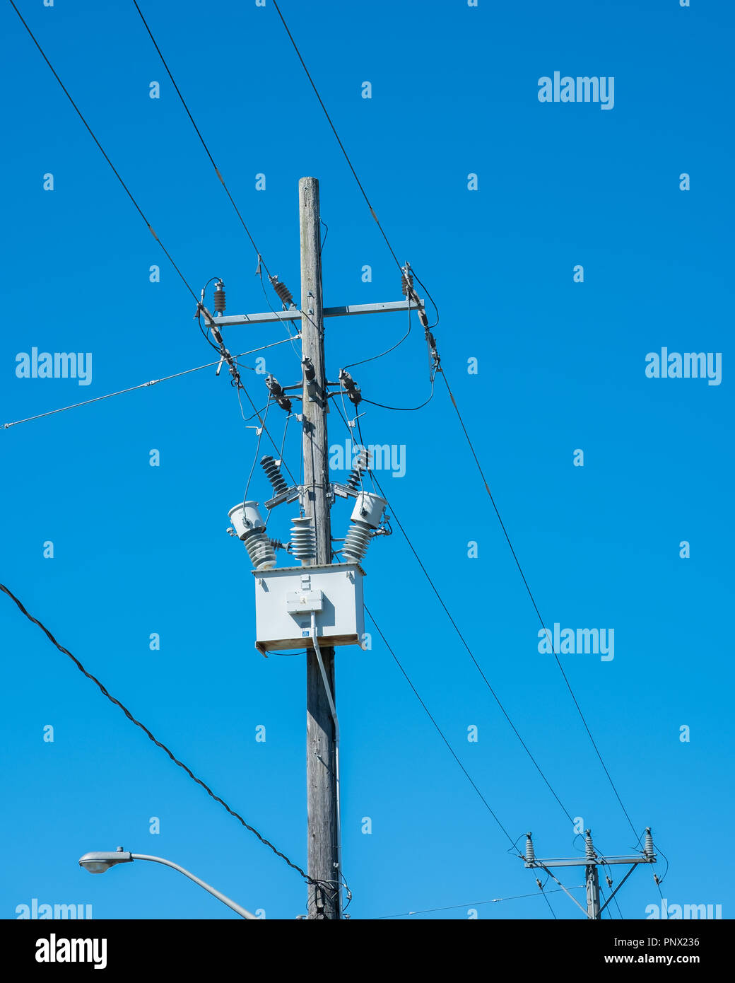 High voltage wires and a transformer box against a clear essential services, service, blue sky with copy space. - Stock Image