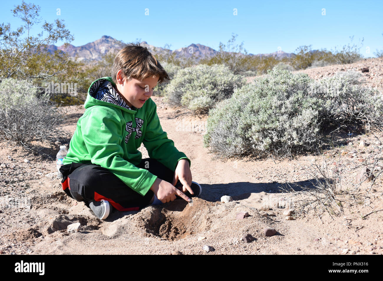 school age boy sitting on the ground building with dirt in the nevada desert - Stock Image