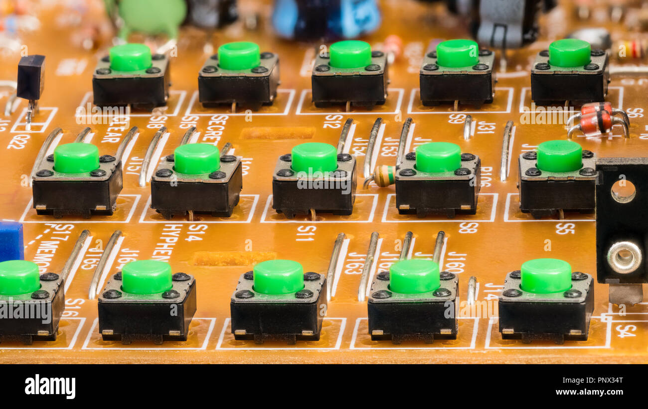 Dismantled VoIP phone keypad. Buttons on circuit board. Green plastic pushbuttons close-up. Electronic components in disassembled telephone keyboard. - Stock Image