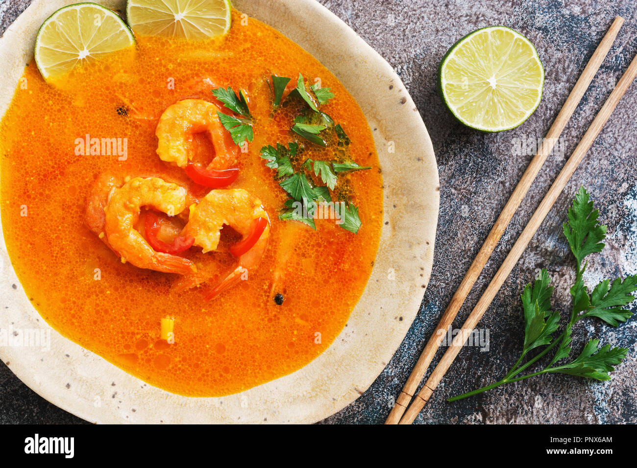 Spicy sour soup with prawns (Tom Yum Goong) on a rustic background. Thai food. View from above, flat lay - Stock Image