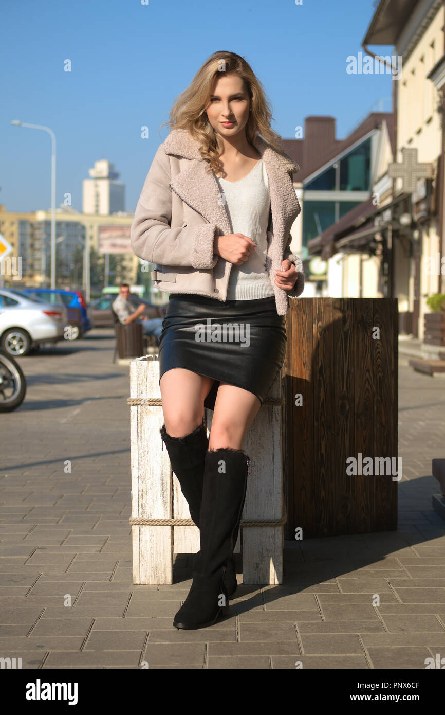 2edbfe9aea Attractive girl in short sheepskin coat, leather skirt and suede boots  having fun in sunny