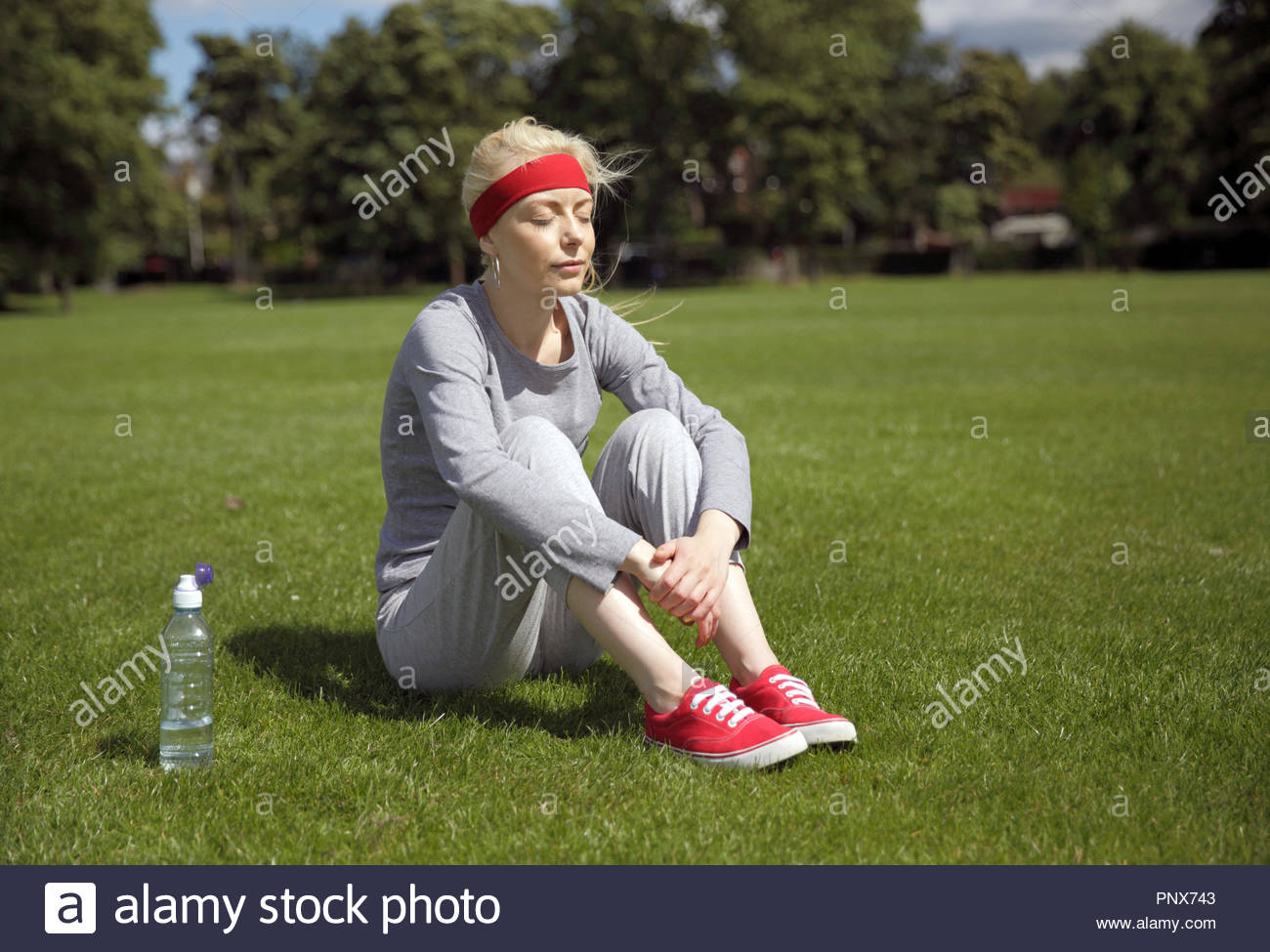 Blonde woman in a tracksuit excercising and sitting in the park - Stock Image