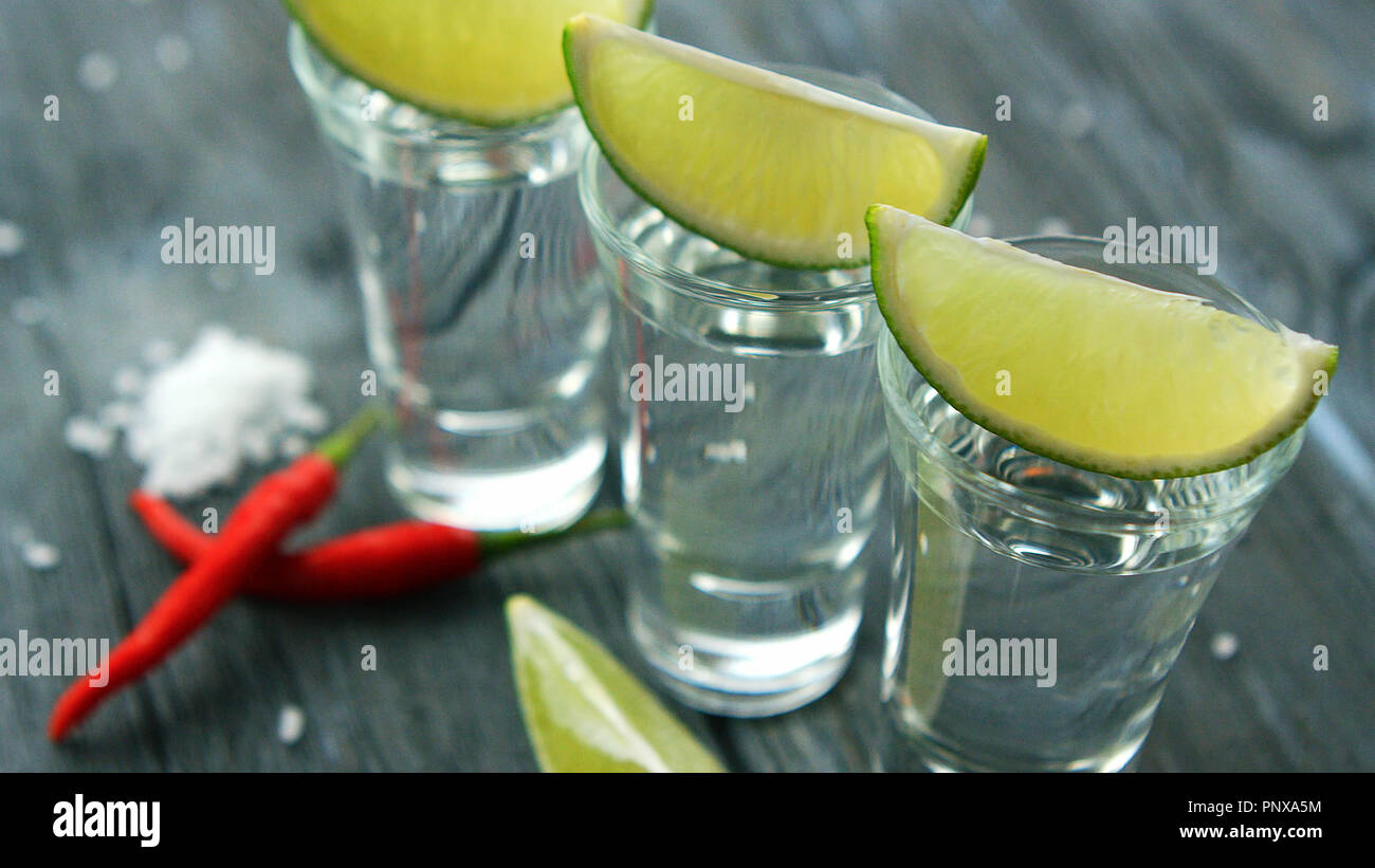Served shots with tequila and lime slices - Stock Image