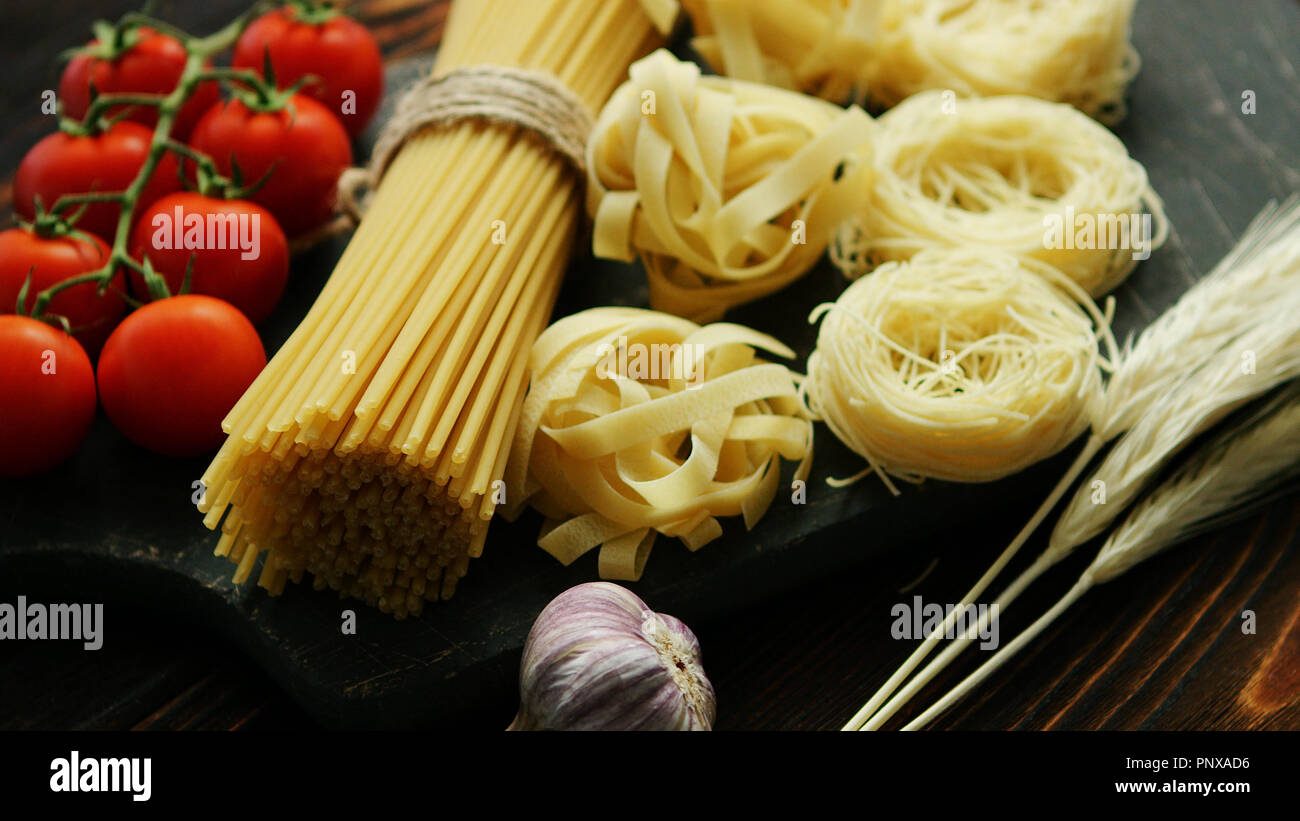 Dry pasta assortment on board - Stock Image