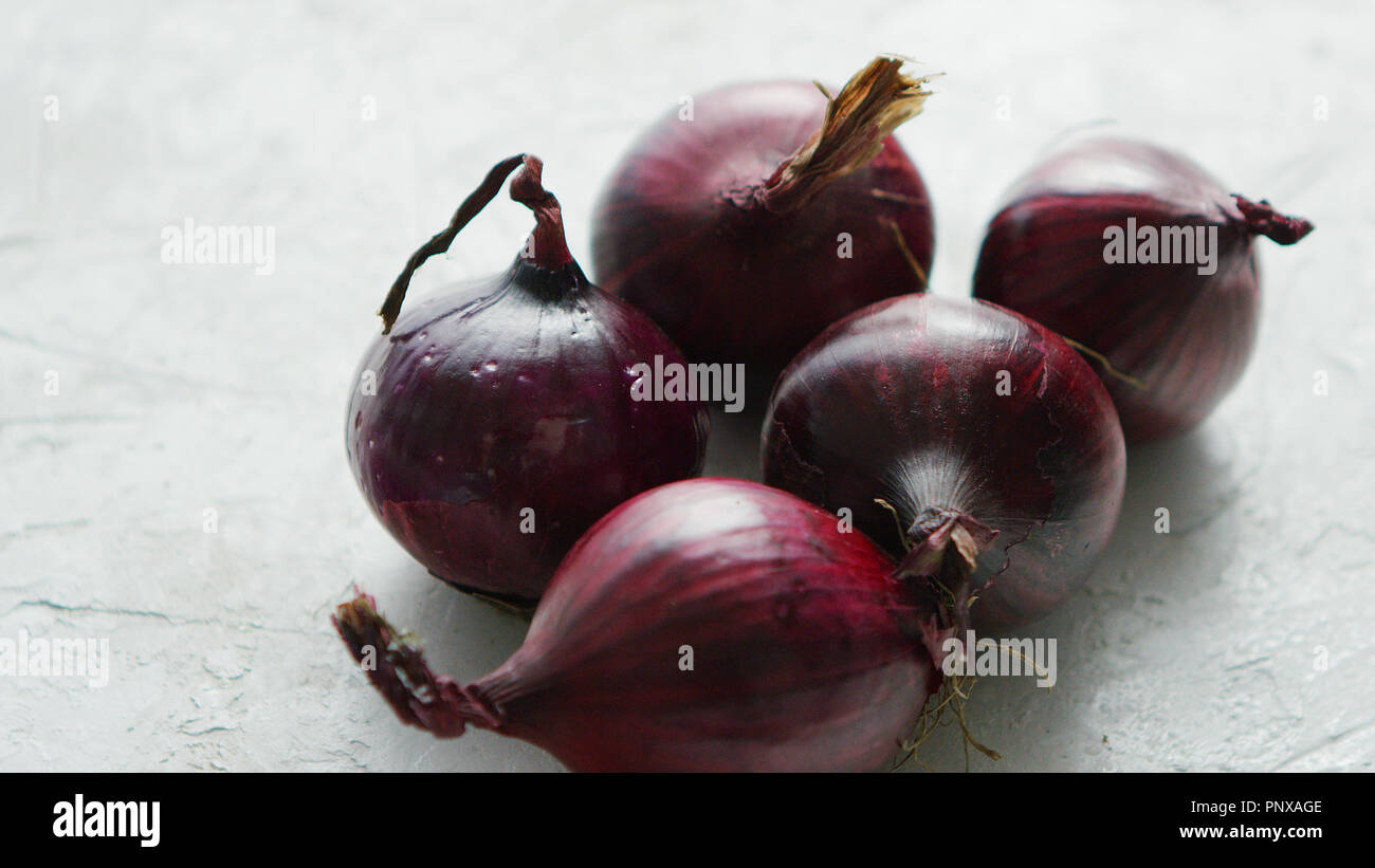 Red onion bulbs on white table - Stock Image