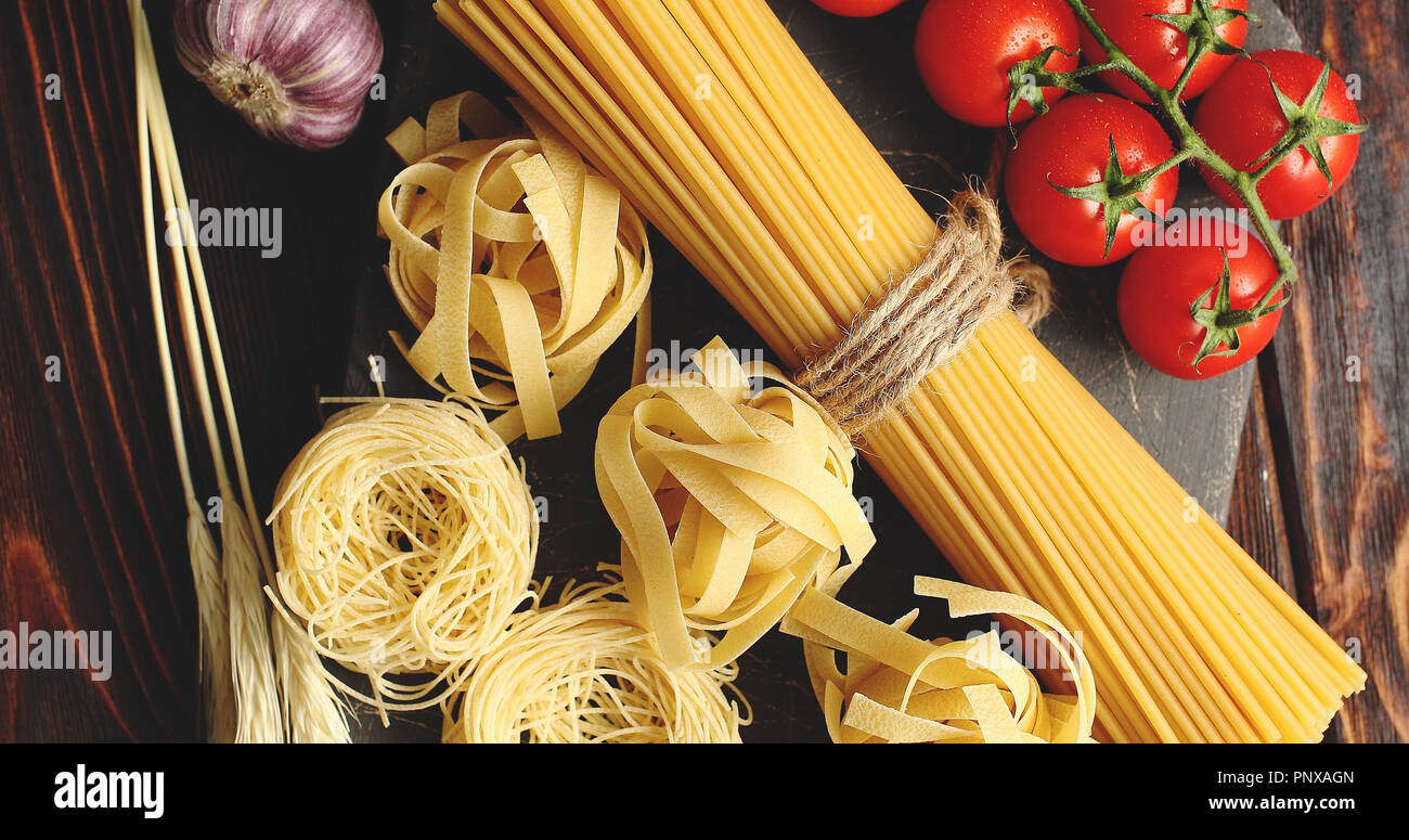 Various pasta and tomatoes with garlic - Stock Image