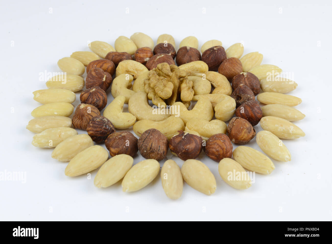 Mixed nuts ordered in flower or sun shape - Stock Image