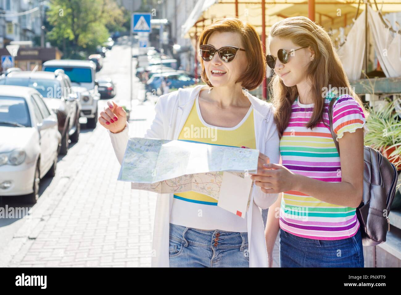 Mom and daughter teenager tourist looking at the map on the street of european city, travel to Europe - Stock Image