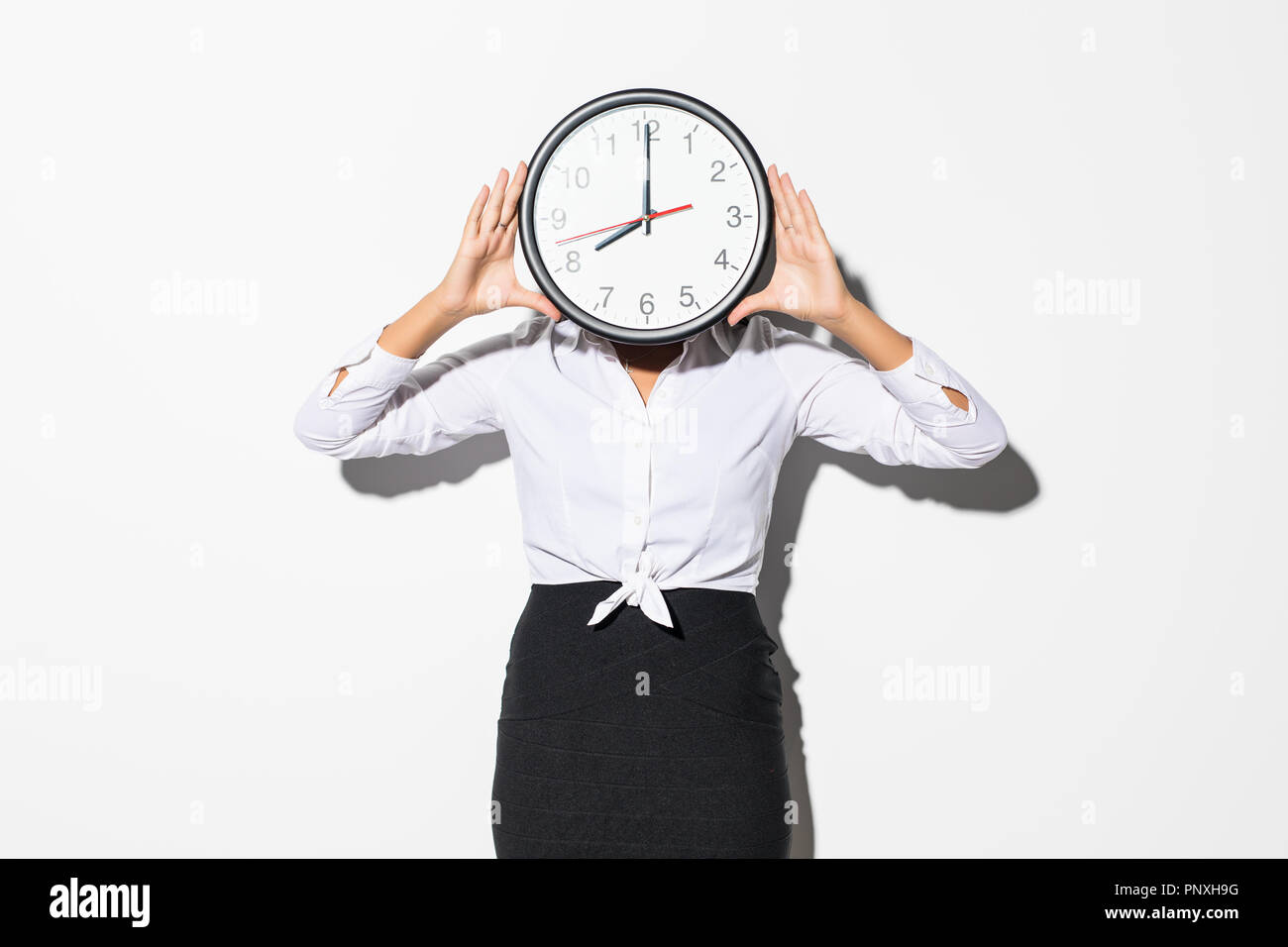 Photo of funny woman in white shirt and black skirt covering face with big round clock isolated over gray background - Stock Image