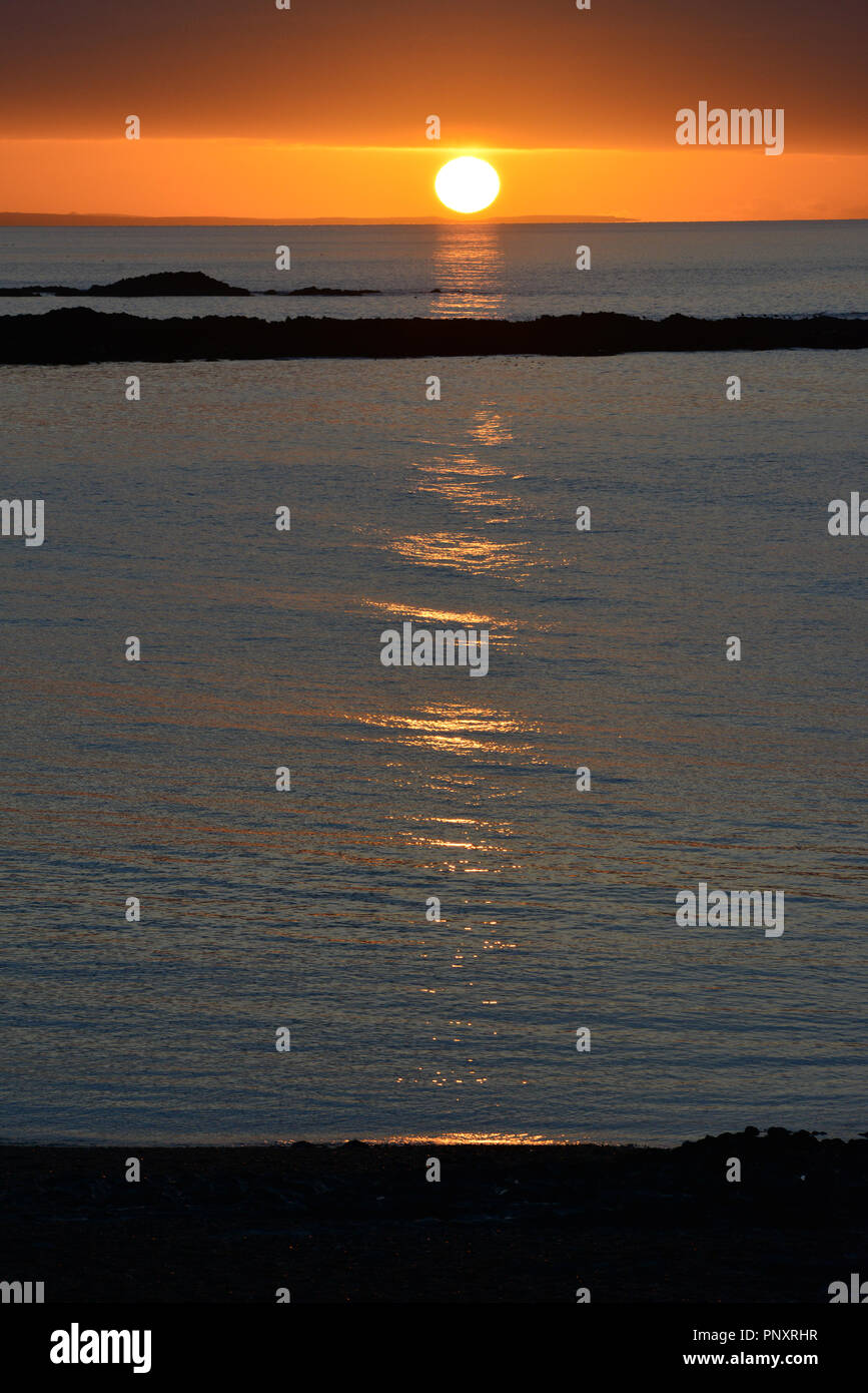 Sunset over Cardigan Bay from the promenade in Aberystwyth, Wales, UK - Stock Image