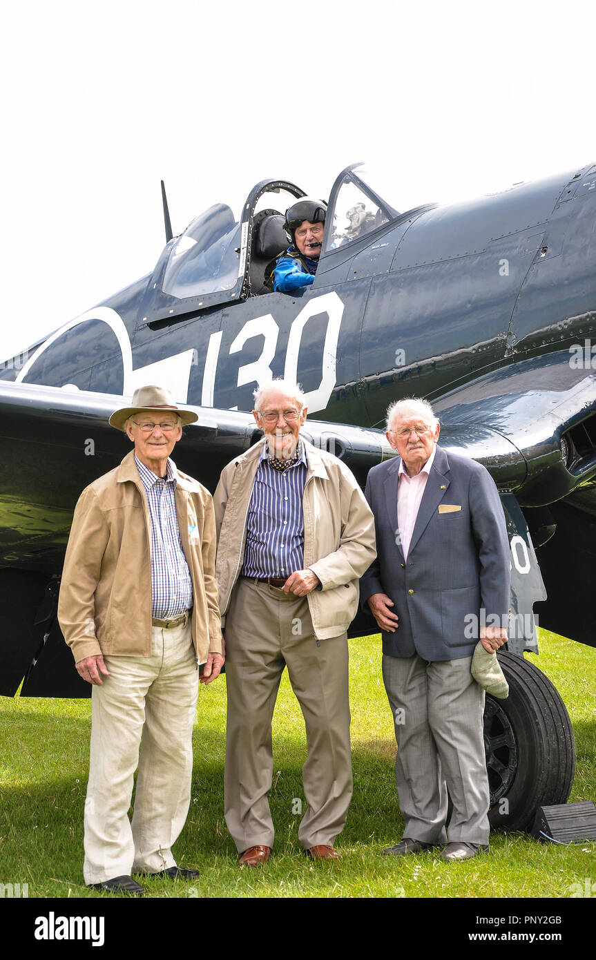 Veteran pilots Keith Quilter, Christopher Cartledge and Peter George with Stephen Grey in The Fighter Collection Goodyear Corsair WWII fighter plane - Stock Image