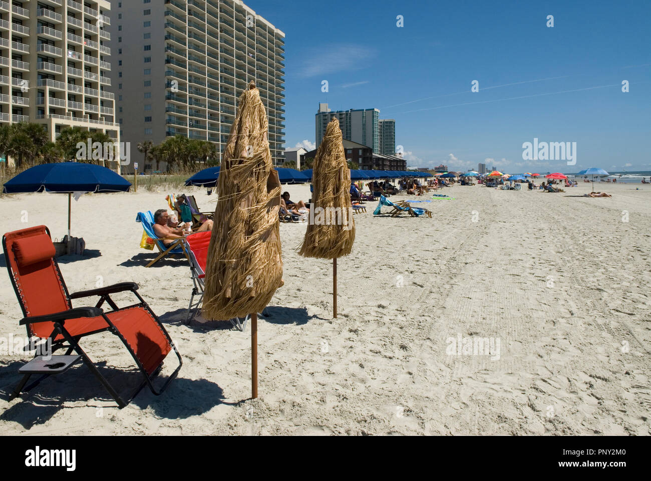 Umbrella and blue chair on beach at North Myrtle Beach South Carolina USA - Stock Image