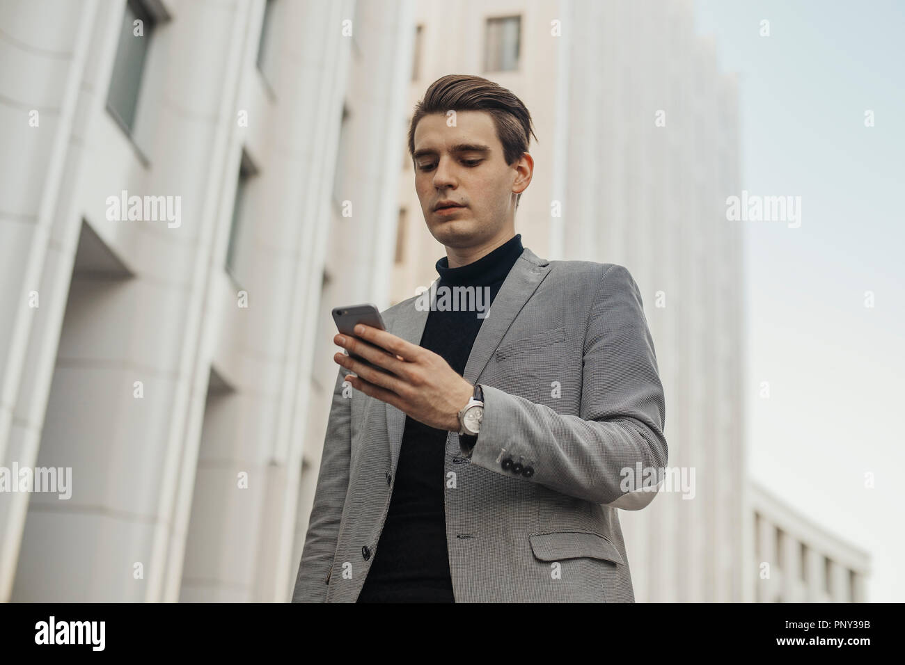 Close up of young businessman talking by mobile phone next to business center. - Stock Image