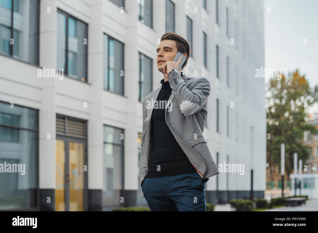 Distant plan of young businessman talking by mobile phone next to skyscraper. - Stock Image