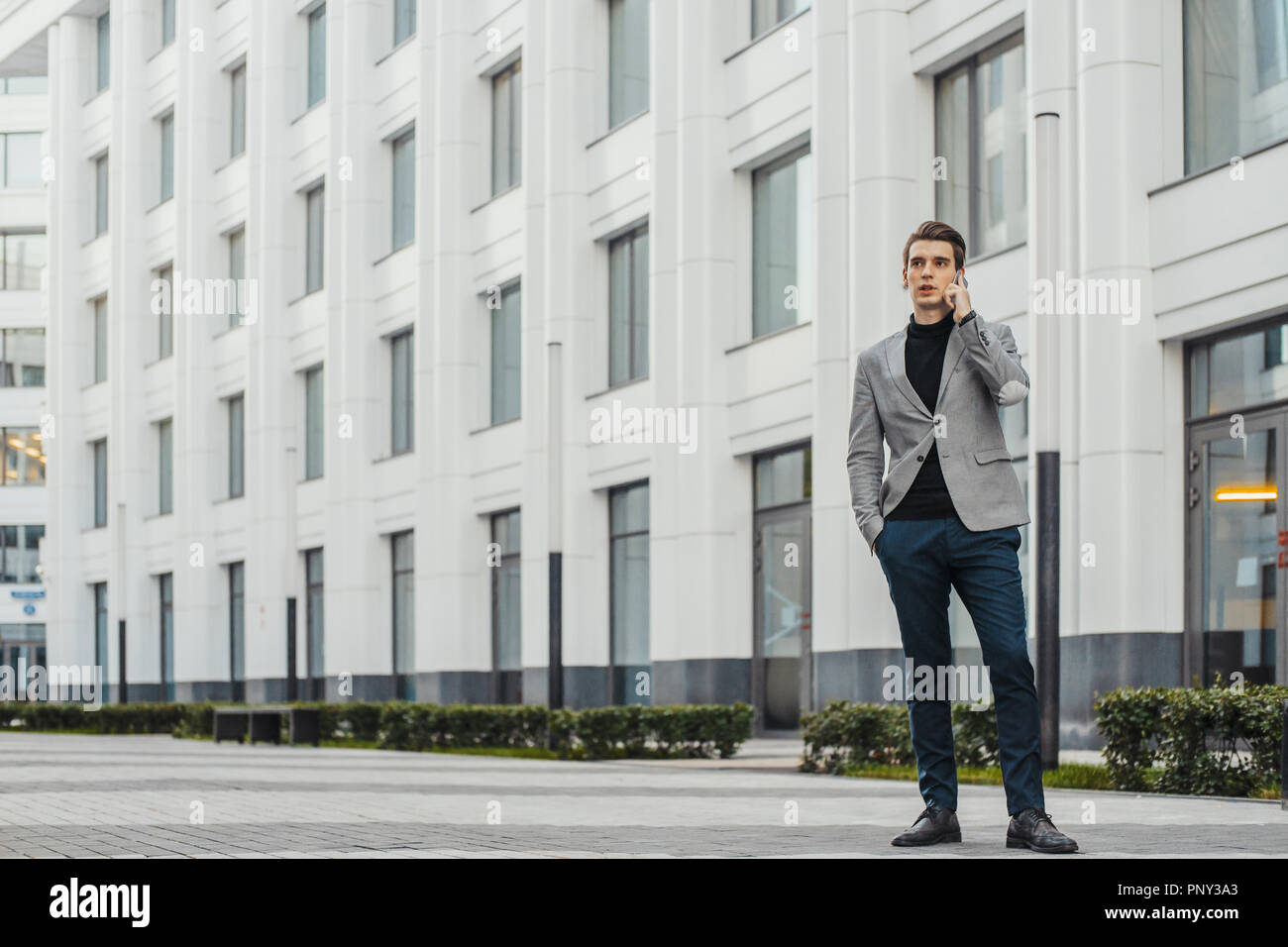 Young businessman talking by mobile phone next to business center. - Stock Image
