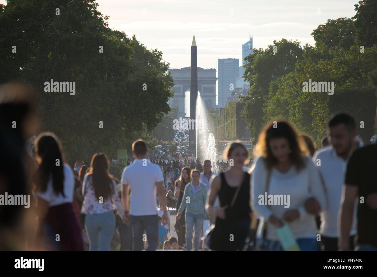 People visiting Place de la Concorde with in the background a beautiful superposition of the obelisk and Arc de Triomphe - Stock Image