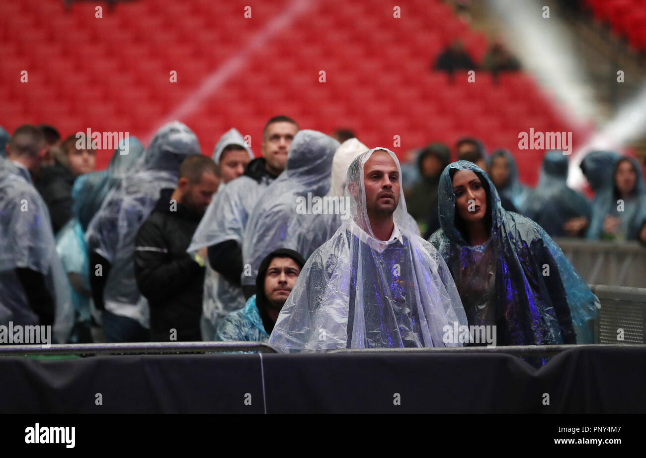 Spectators in rain ponchos during the Heavyweight Contest Bout at Wembley Stadium, London. - Stock Image