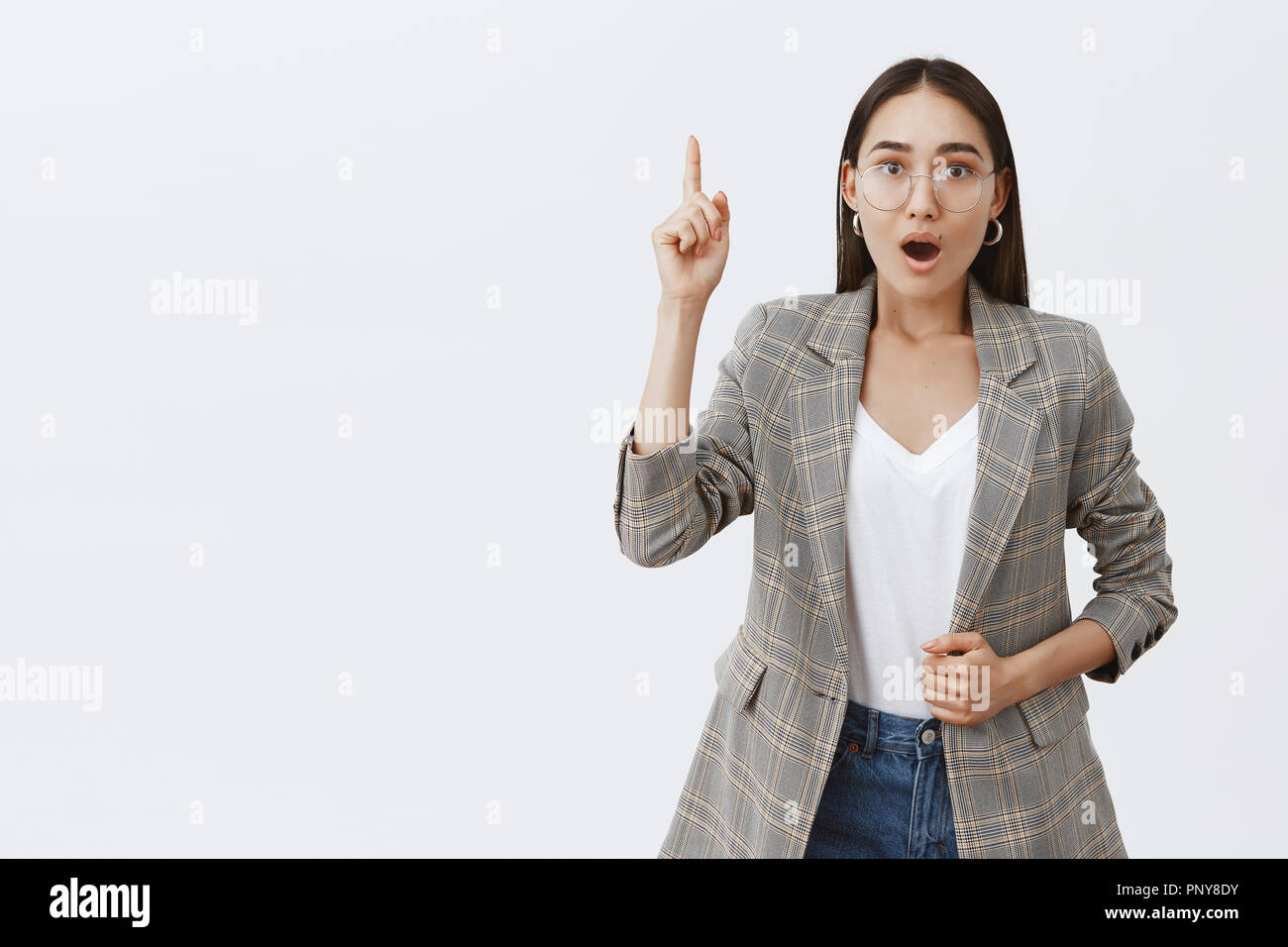 Girl finally have idea, adding suggestion during office meeting. Intense thrilled adult female in glasses and jacket, lifting index finger in eureka gesture, gasping, saying interesting thought - Stock Image