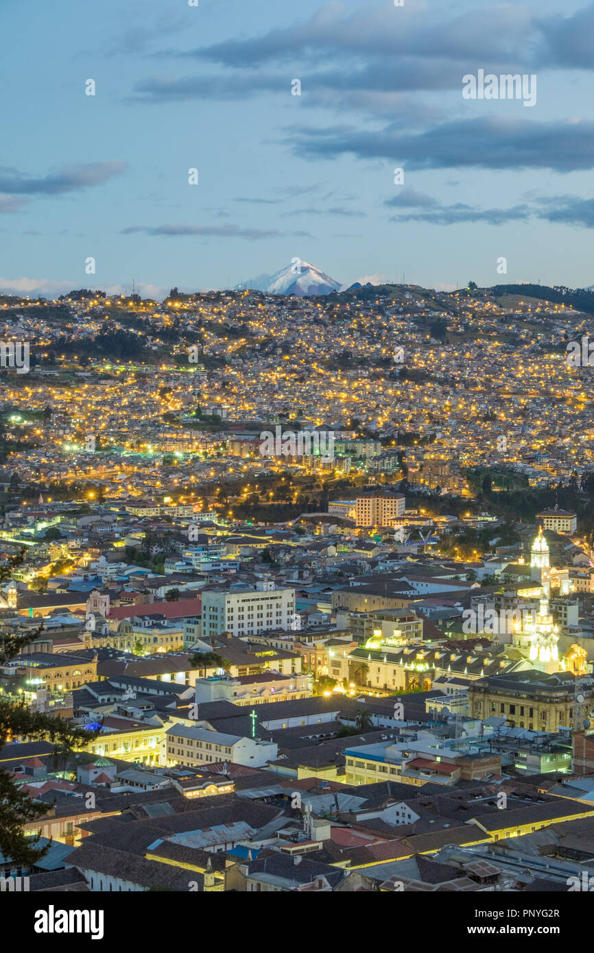 View of Quito at night and Cotopaxi volcano in the background, Ecuador - Stock Image