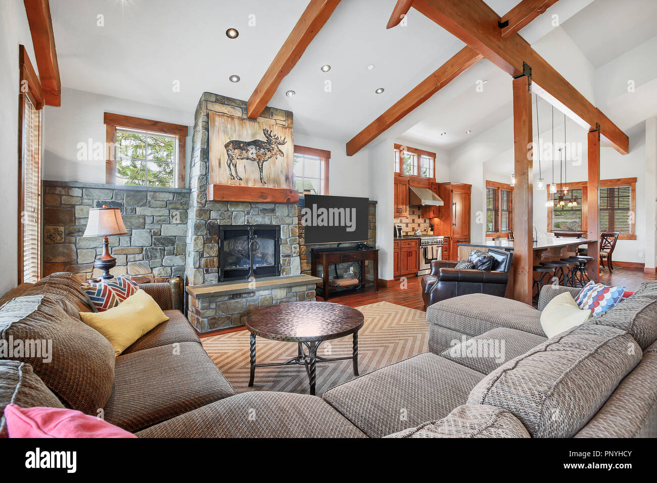 Beautiful Open Plan Home With A Well Styled Living Room, Stone Fireplace, Vaulted  Ceiling With Beams And Hardwood Floor.