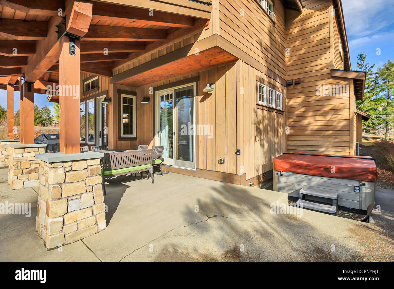Wooden Home Exterior With Spacious Back Patio, Hot Tub And Barbecue.