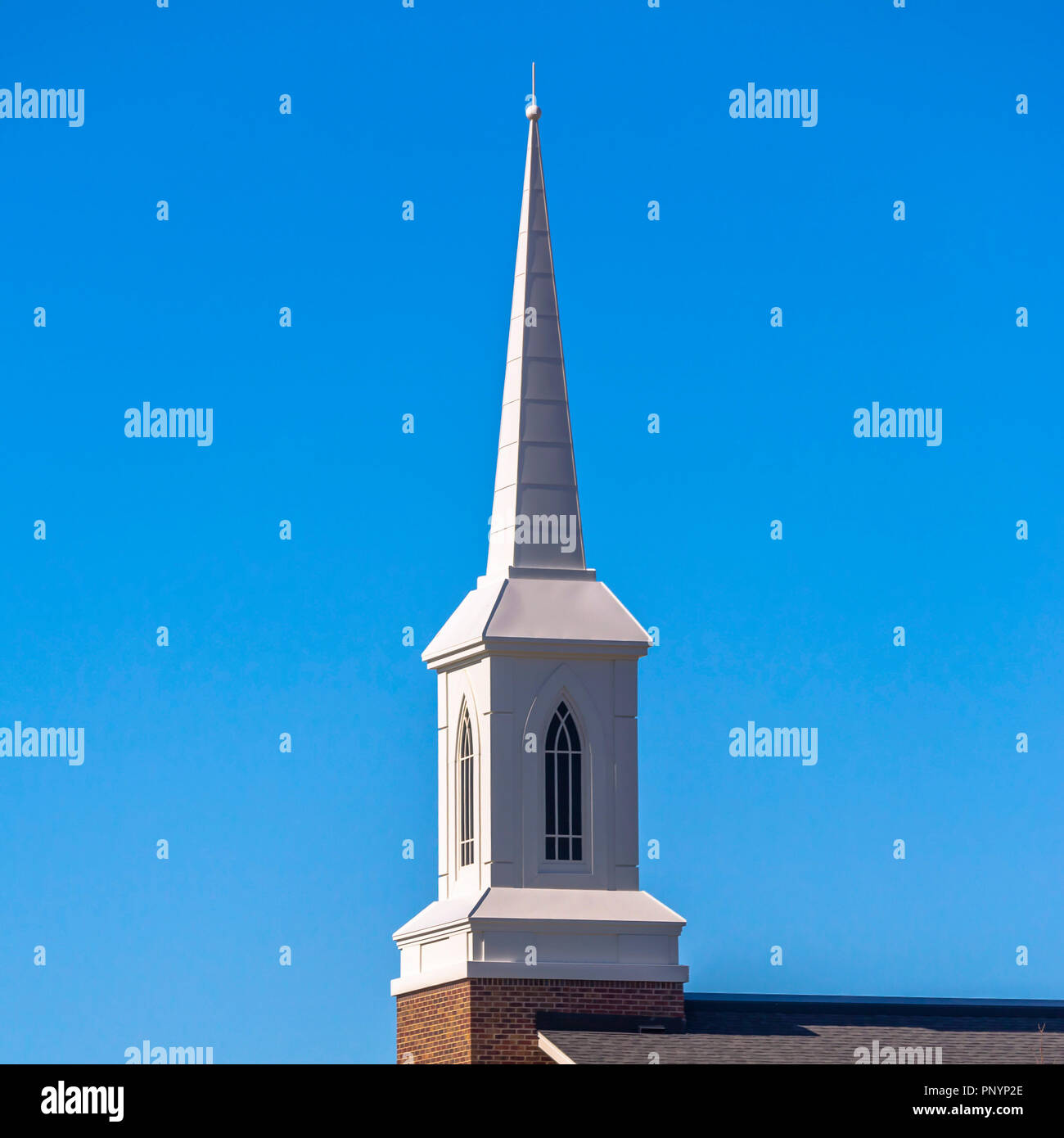Steeple with arched windows against blue sky - Stock Image