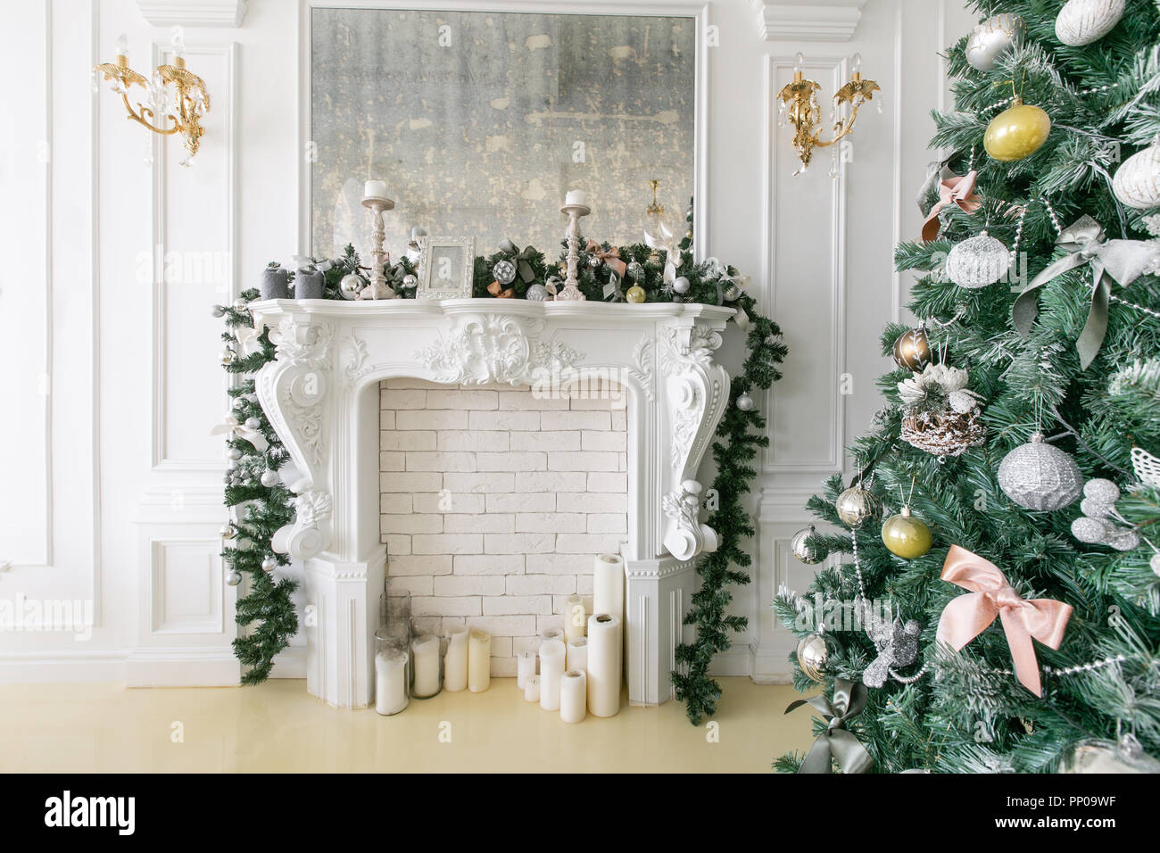 White fireplace decorated with candles and fir branches. Decorated ...
