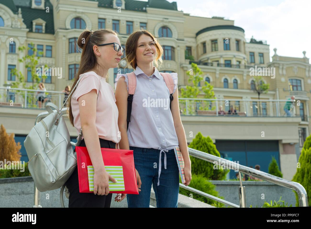 Back to school. Girls teenagers with backpacks and textbooks go to school - Stock Image