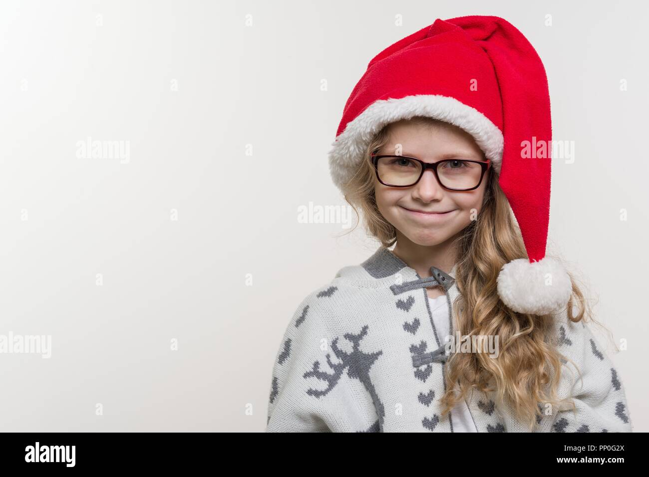 2001f209479 Winter holidays - an open portrait of funny girl of 7 years in a Santa Claus