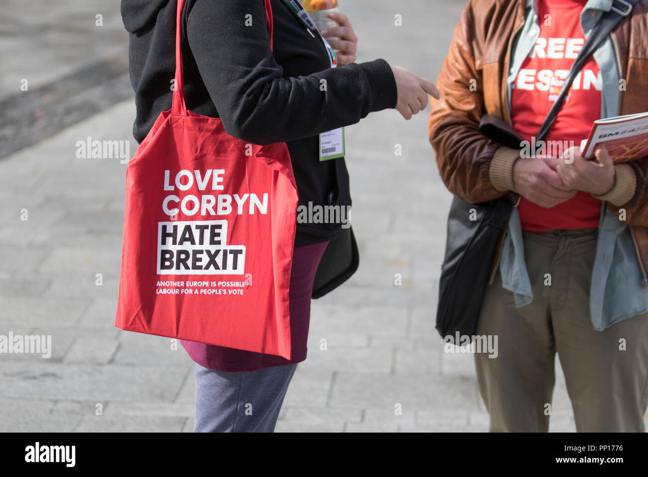 Liverpool, Merseyside.  UK Weather 23/09/2018. Sunshine & showers greet delegates to the Labour Party Conference who have been given a red cloth shoulder bag lettered 'Love Corbyn Hate Brexit'  Credit; MediaWorldImages/AlamyLiveNews - Stock Image