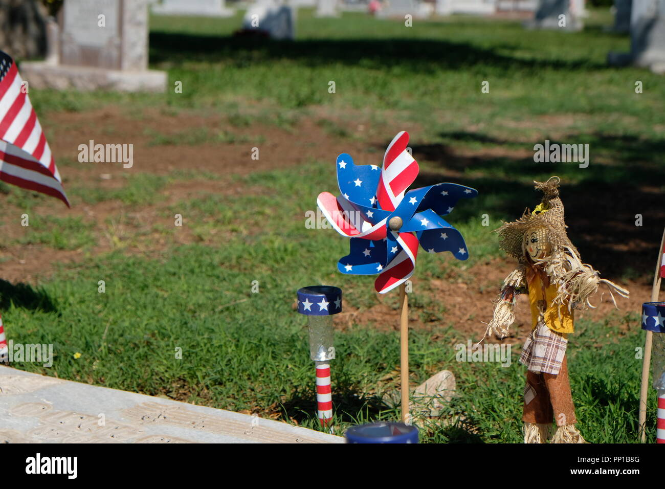 patriotic pinwheel and scarecrow on a burial plot in the city of