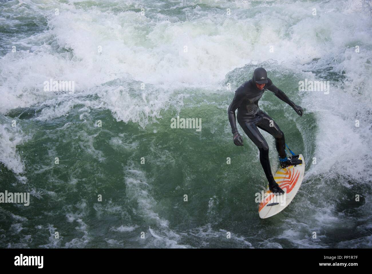 A surfer rides the continuous wave in the Eisbach river in the Englischer Garten city park. - Stock Image