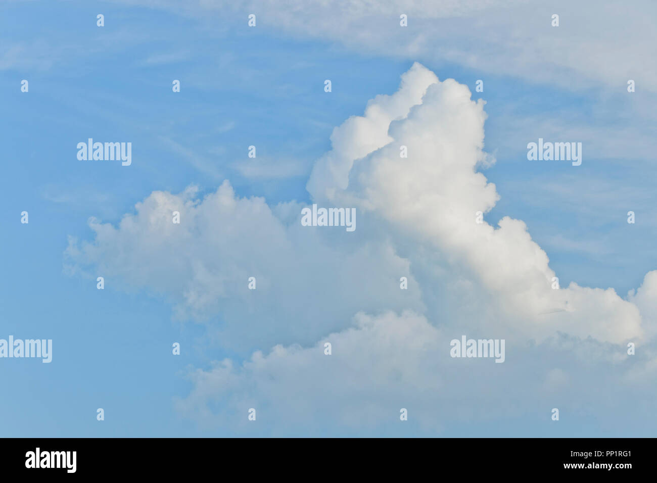 Puffy and rolling clouds in the late-afternoon summer sun. - Stock Image