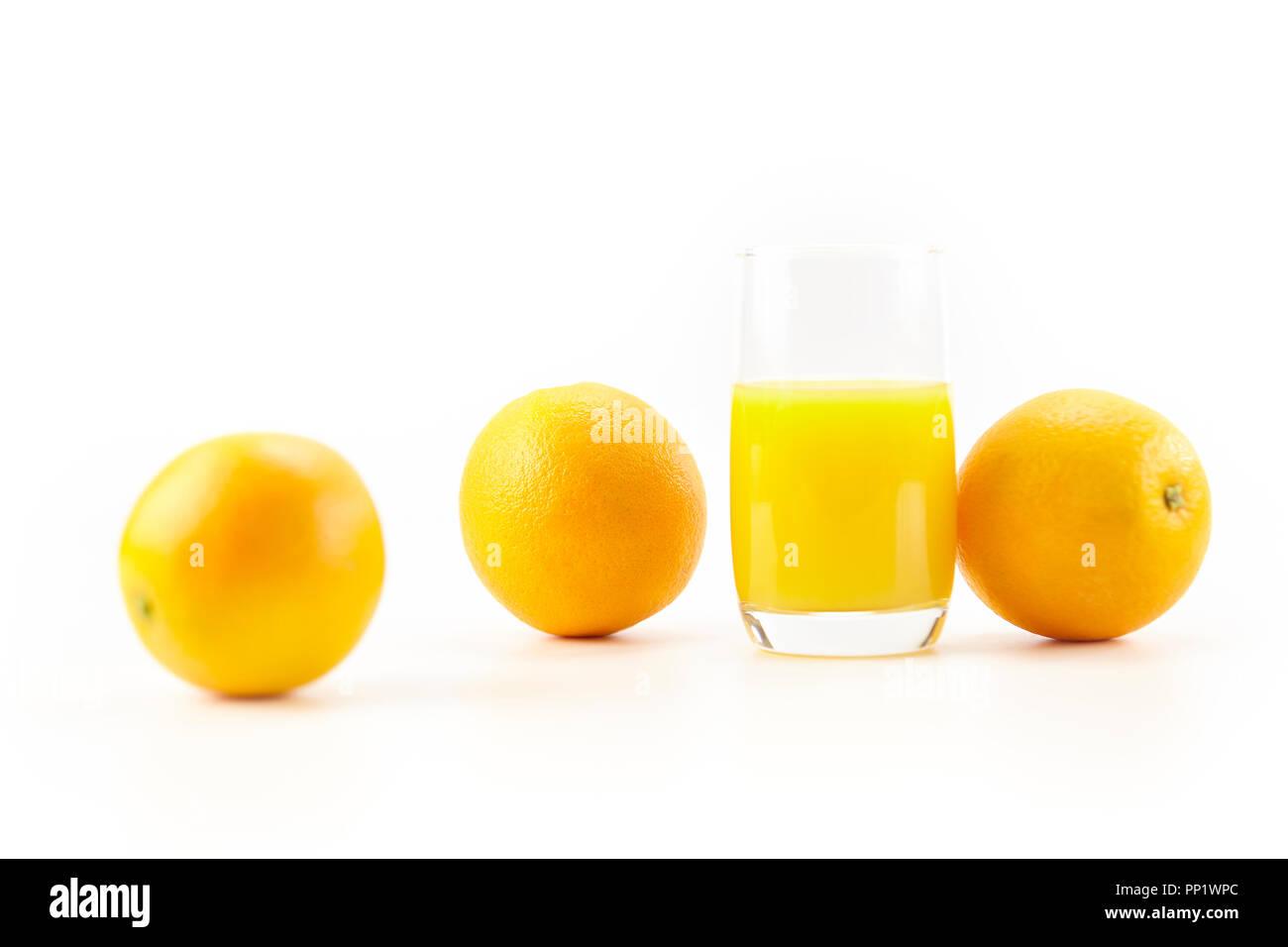 three oranges and a glass of orange juice isolated on white background. - Stock Image