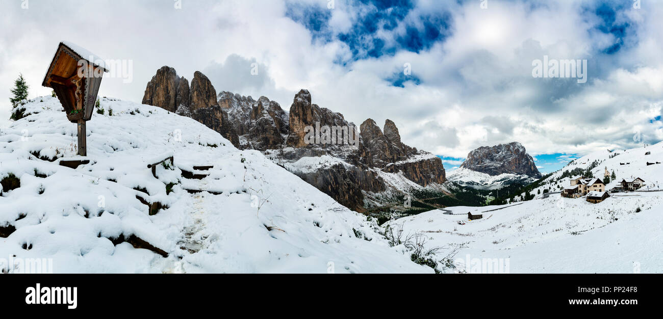 Mountain street of Gardena Pass with snowy landscape on the mountains of Group of Sella and cloudy sky, Gardena Valley - Trentino-Alto Adige, Italy - Stock Image
