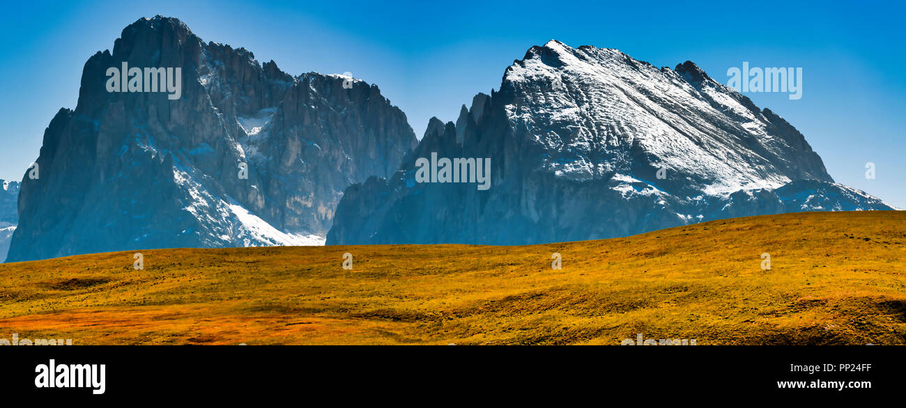 Group of Langkofel with first snow of season and orange hill in foreground in a clear day and blue sky, South Tyrol - Italy - Stock Image