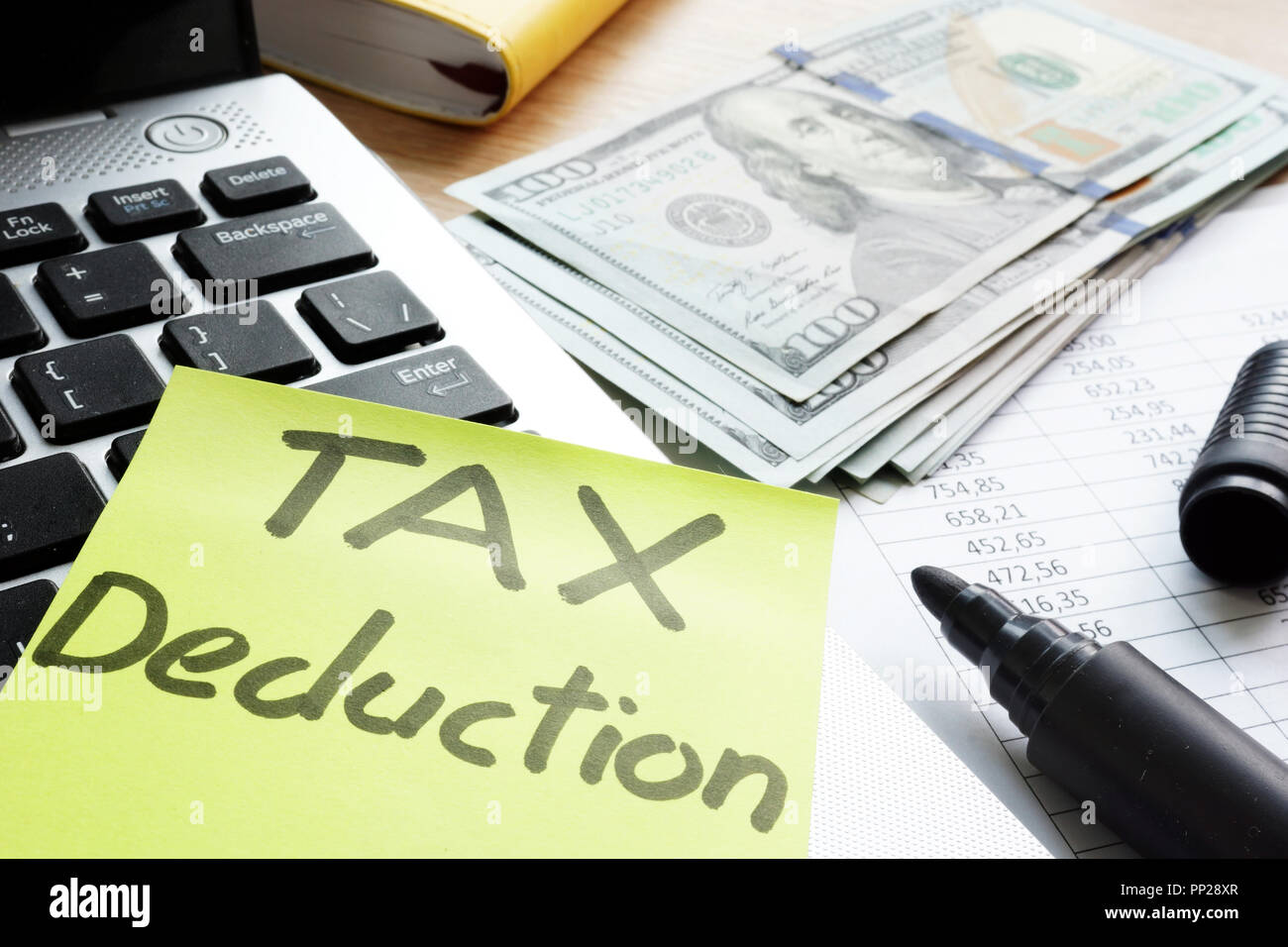Tax deduction written on a memo stick. - Stock Image