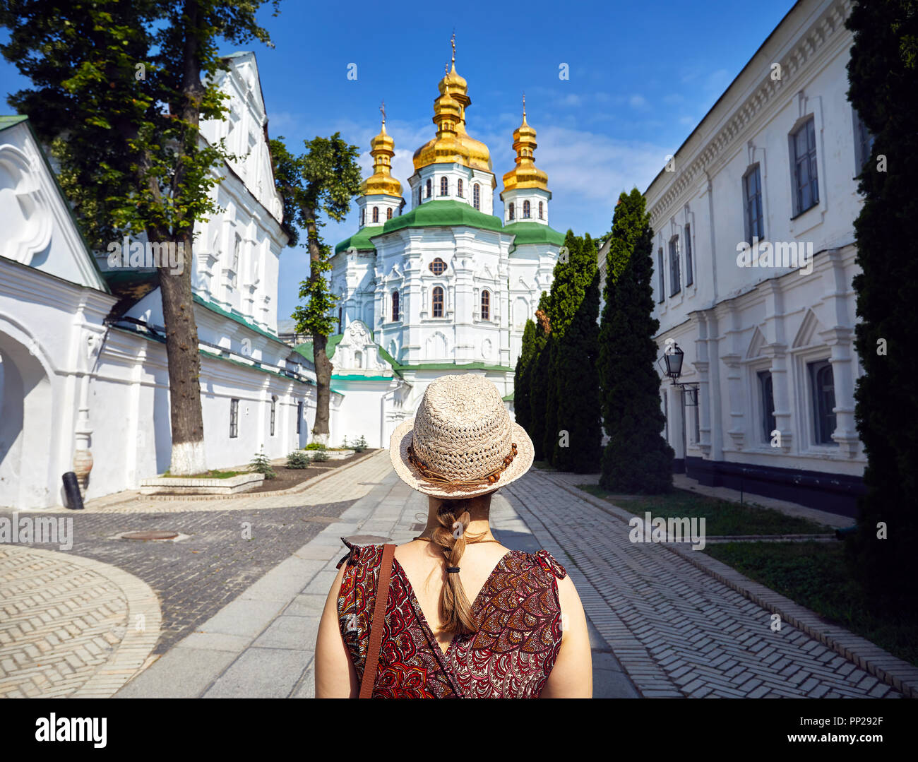 Woman in hat looking at Church with golden domes at Kiev Pechersk Lavra Christian complex. Old historical architecture in Kiev, Ukraine - Stock Image
