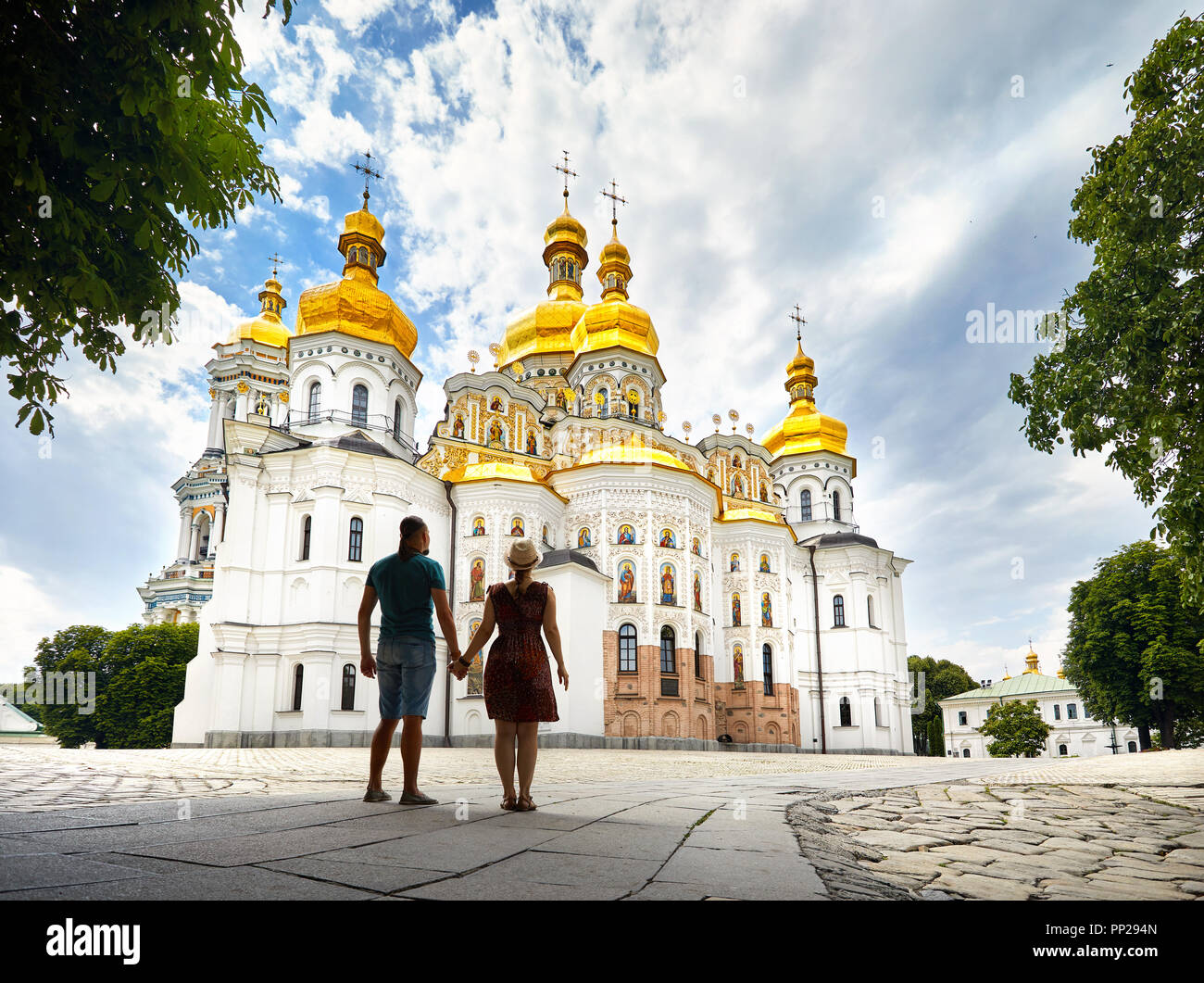 Young tourist couple in silhouette looking at Church with golden domes at Kiev Pechersk Lavra Christian complex. Old historical architecture in Kiev,  - Stock Image